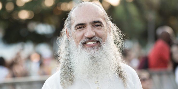 Com trajes brancos e cabelos longos; o líder espiritual Sri Prem Baba sorri para a fotografia